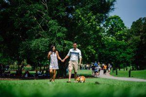 Un couple se promène au parc avec leur chien corgi